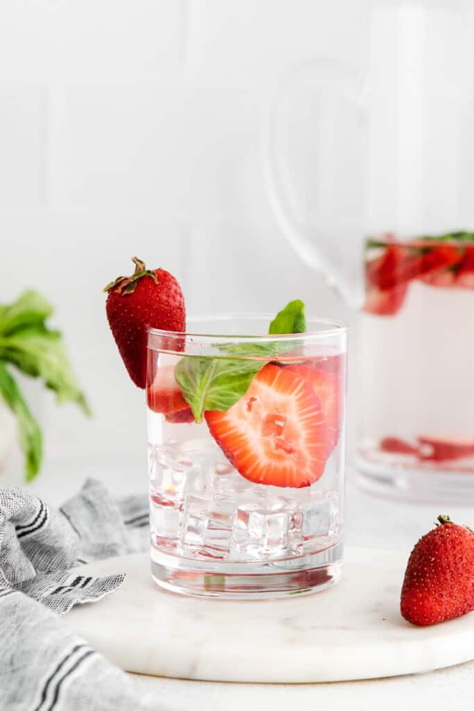 Strawberry and basil infused water in a glass.