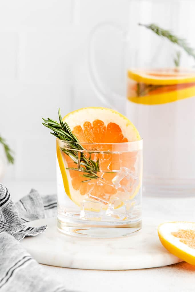 Grapefruit and rosemary infused water in glass.