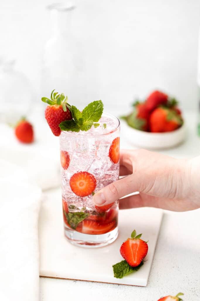 hand holding strawberry mojito