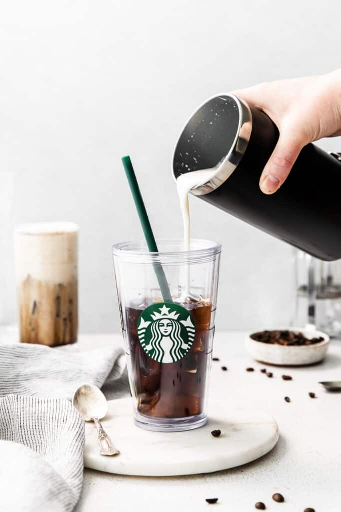Pouring sweet cream into a glass of cold brew.