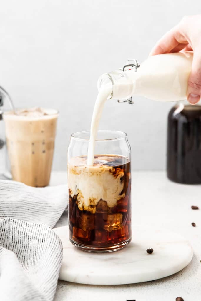 Pouring sweet cream into cold brew.