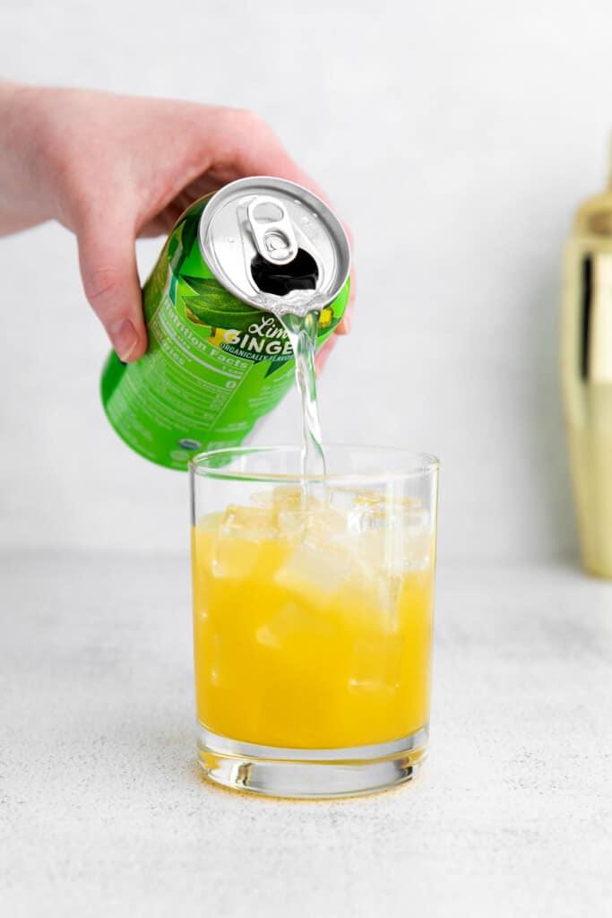pouring sparkling water into a virgin margarita