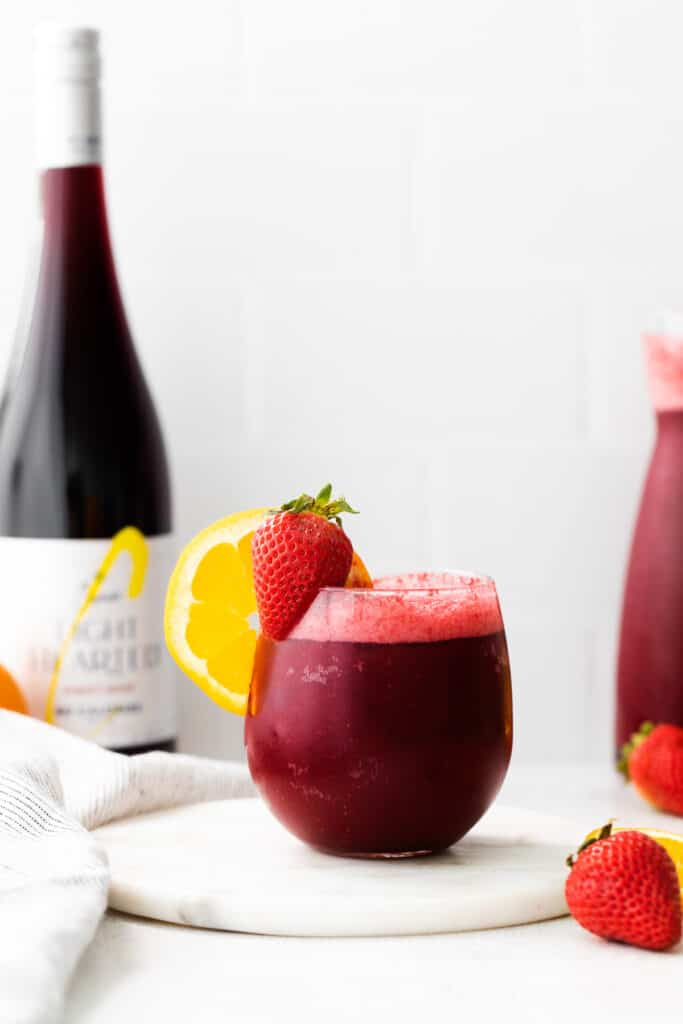 sangria wine slushie in glass with orange and starwberry slices