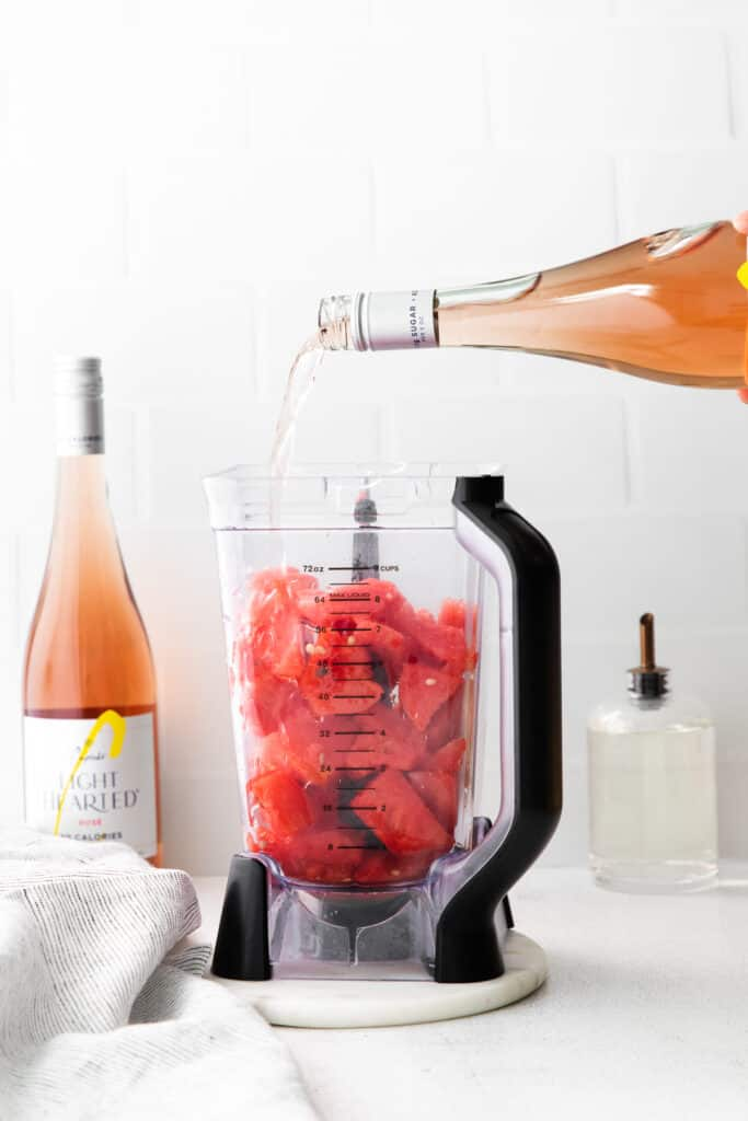 pouring a bottle of rosé into a blender with frozen watermelon