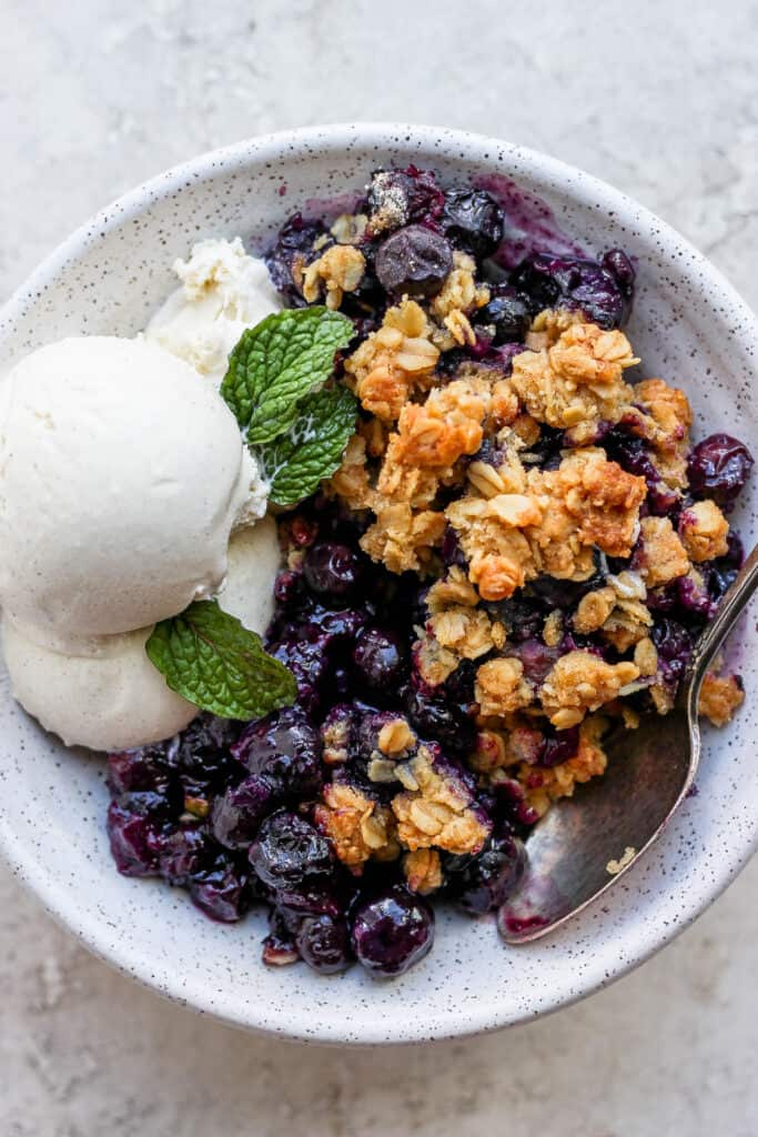 A bowl of blueberry crisp with ice cream.