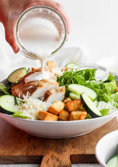 Pouring caesar dressing over a salad.