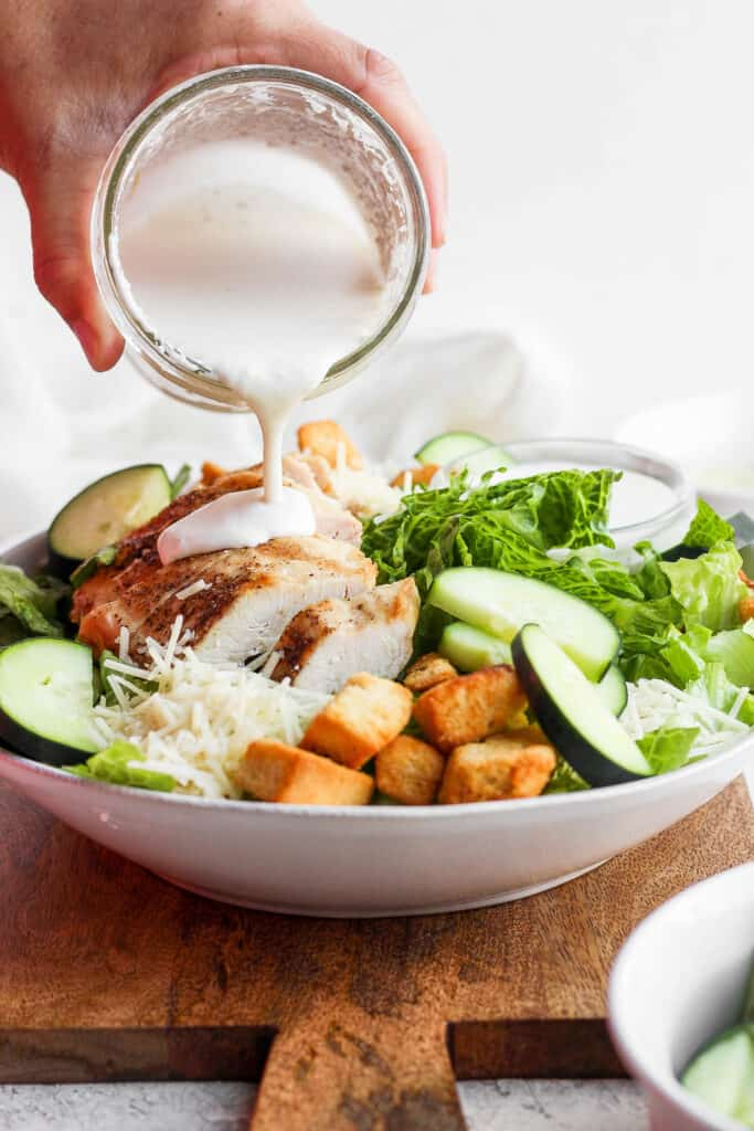 Pouring caesar dressing over chicken caesar salad.