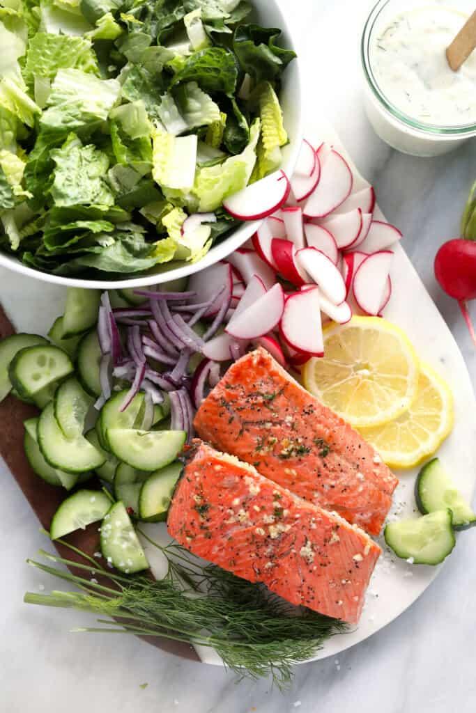 veggies, lemon, and cooked salmon in cutting board