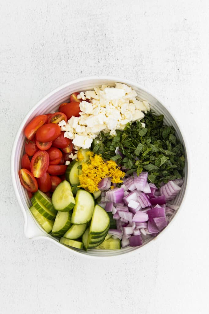 mediterranean cous cous salad ingredients in a bowl