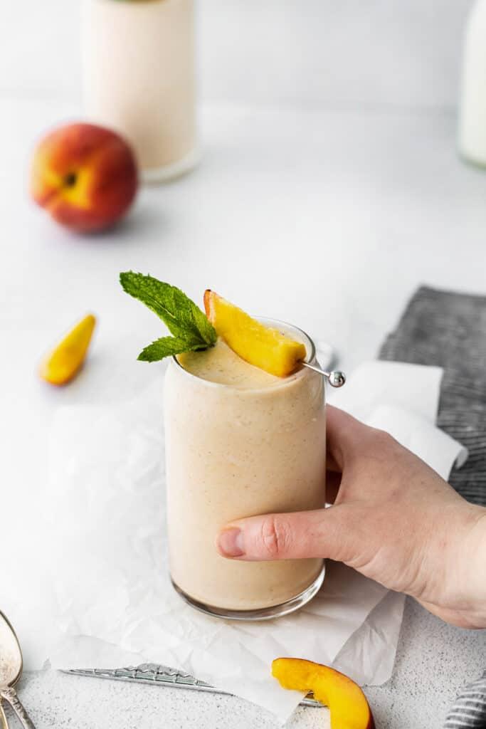 hand holding peach smoothie