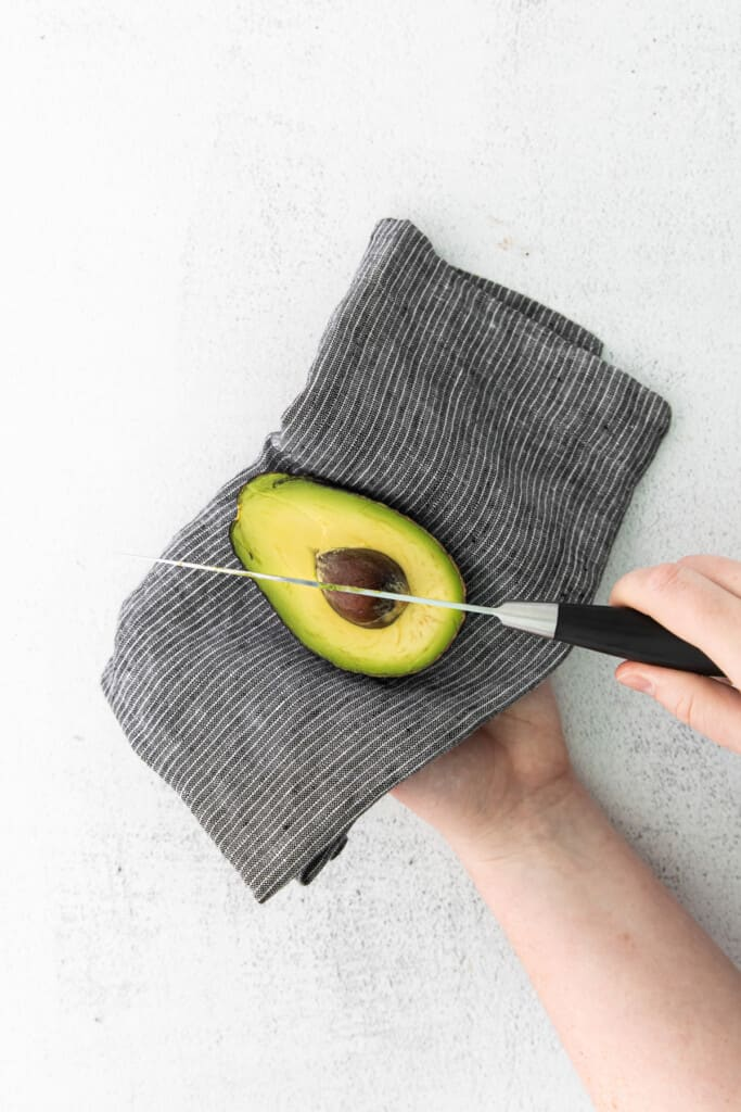 Cutting the pit out of a ripe avocado.