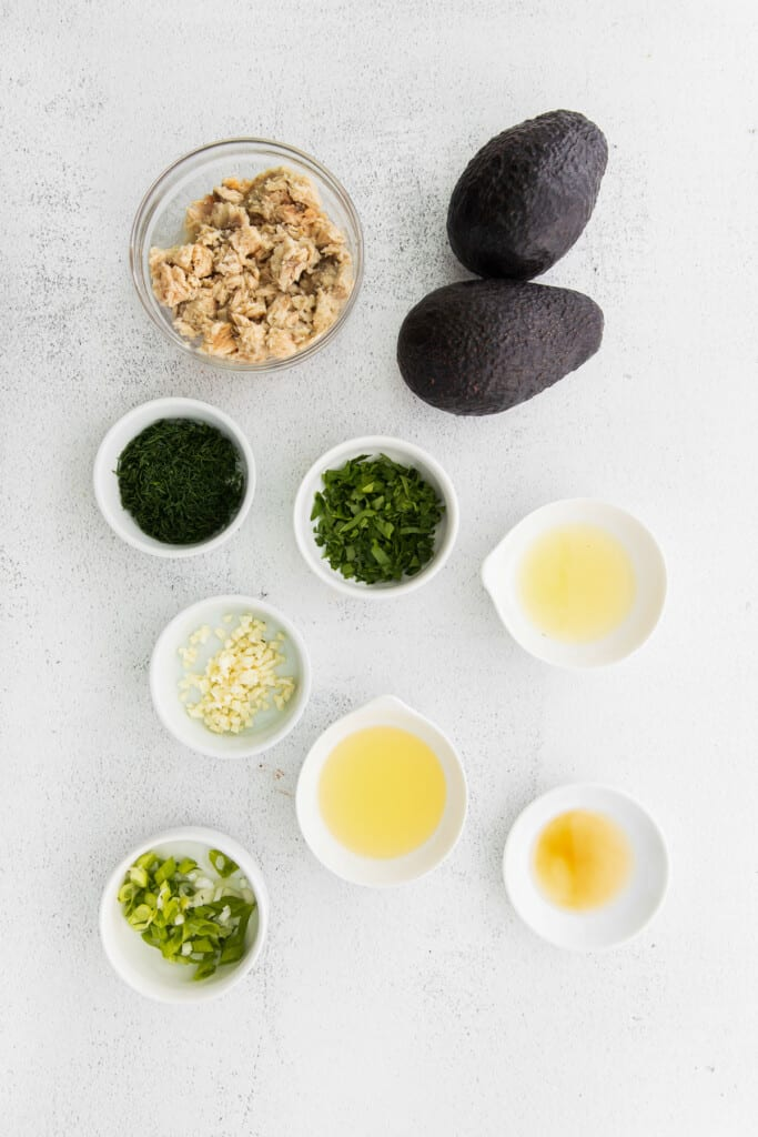 All the ingredients for stuffed avocado boats in small bowls.