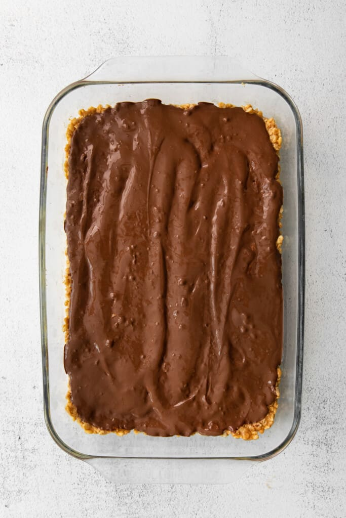 melted chocolate layer of healthy scotcheroos in a baking dish