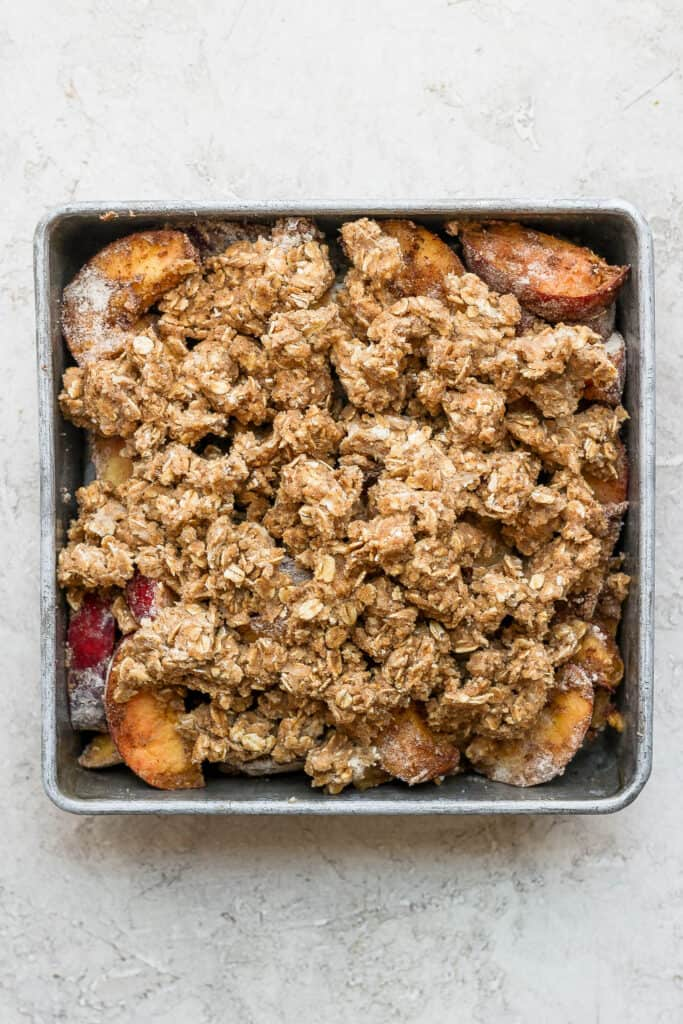peach crisp with crumble topping ready to be baked