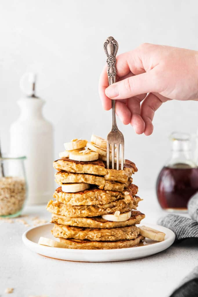 fork biting into pancake stack