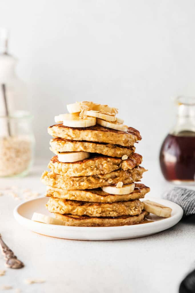 stack of pancakes with banana and oatmeal on top
