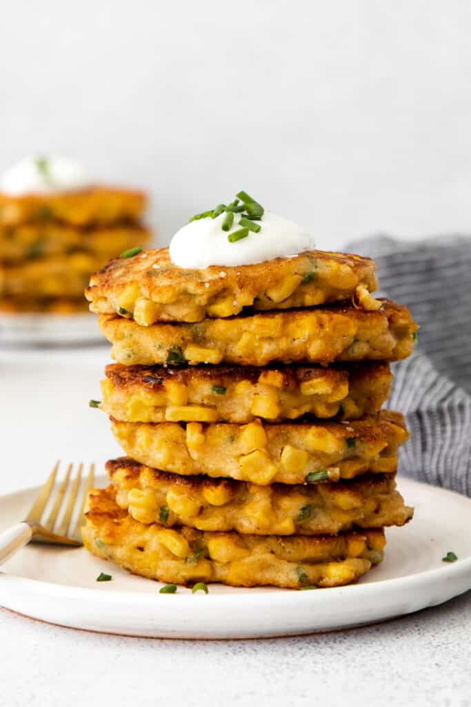 A stack of corn fritters with Greek yogurt and chives on top.