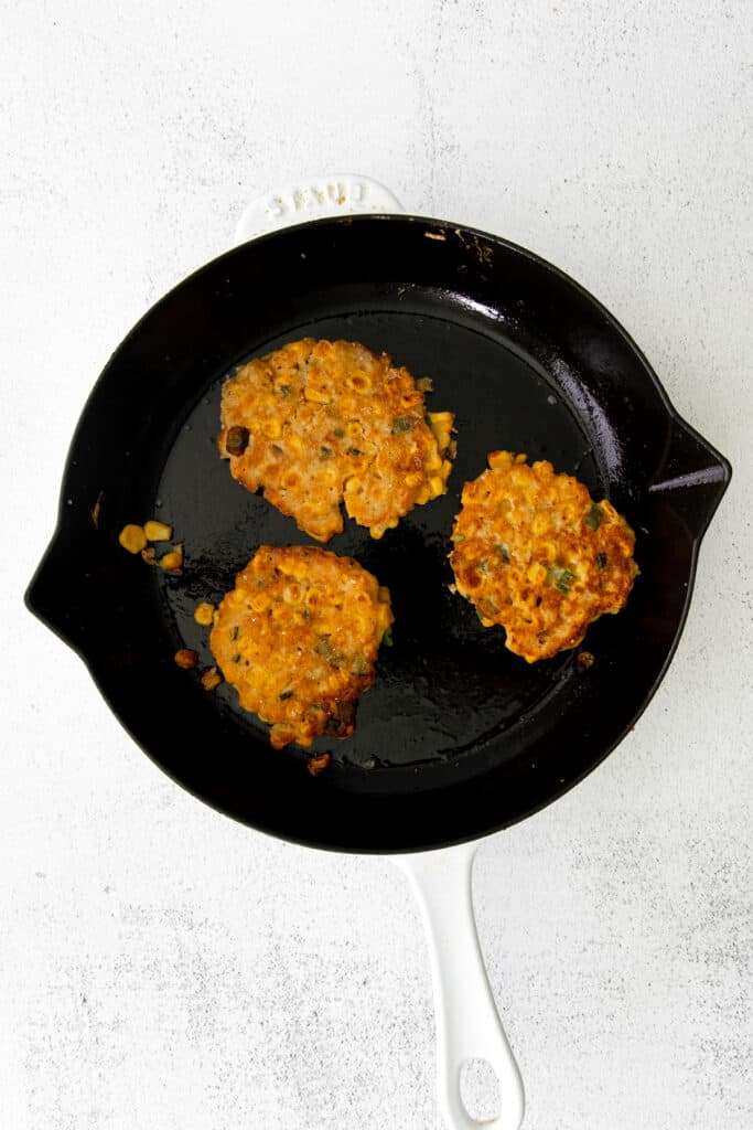 Crispy corn fritters in a cast iron pan.