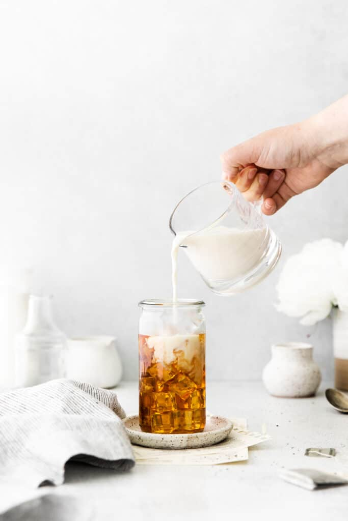pouring milk on top of iced tea