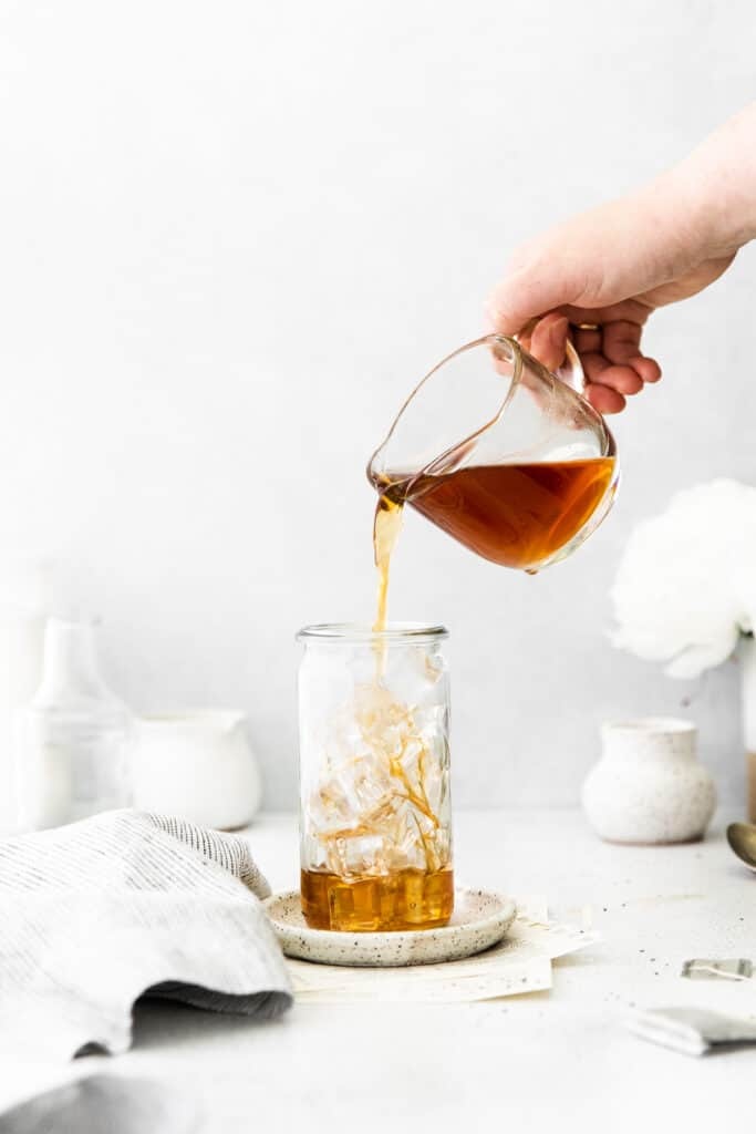 pouring tea into a glass with ice