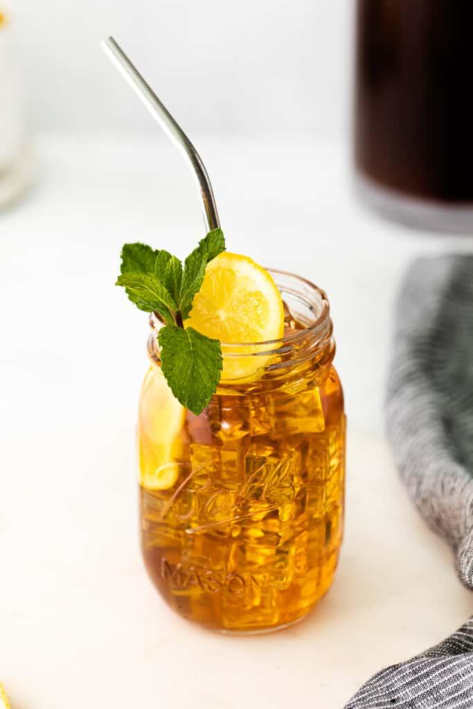 mason jar of iced tea garnished with a slice of fresh lemon and a sprig of fresh mint