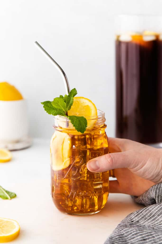 homemade iced tea in a mason jar garnished with mint and a lemon slice