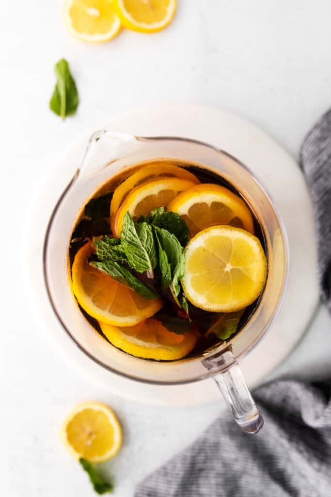 pitcher of iced tea garnished with fresh lemons and mint