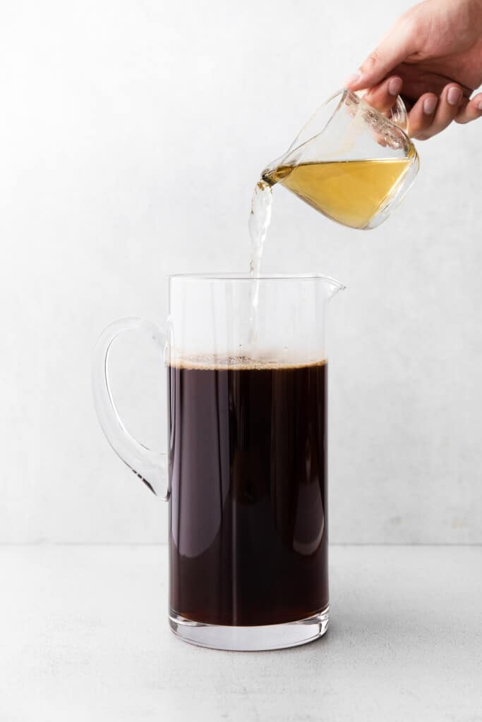 simple syrup being poured into a pitcher of iced tea