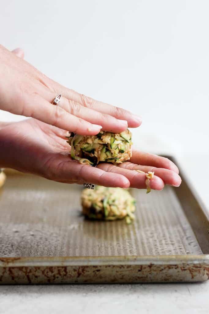pressing cookie dough down in between palms