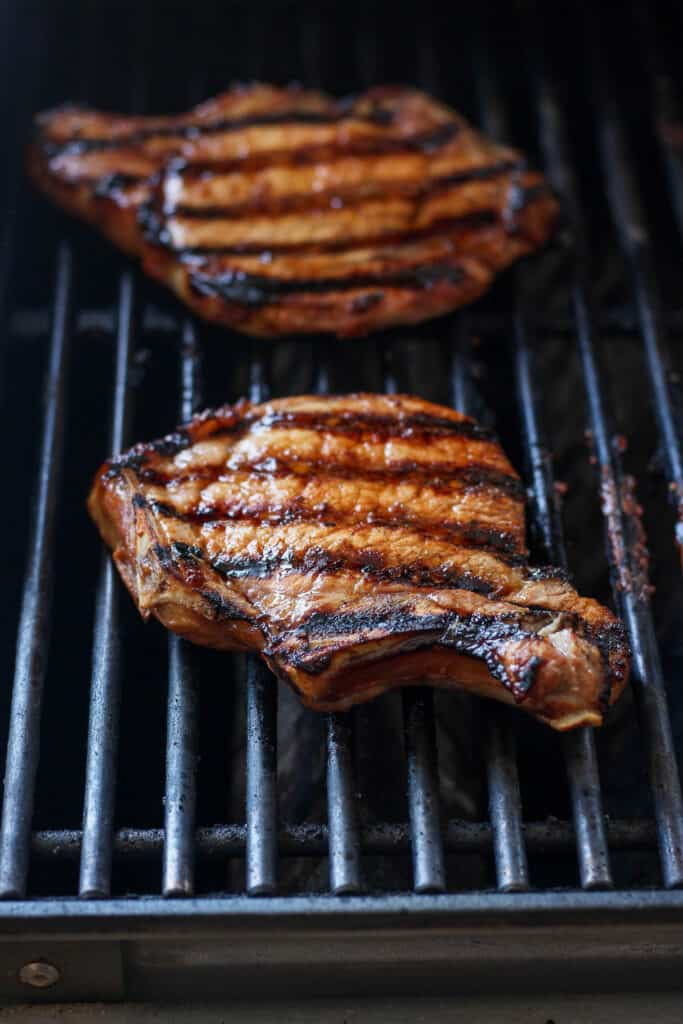 pork chops grilling on grill
