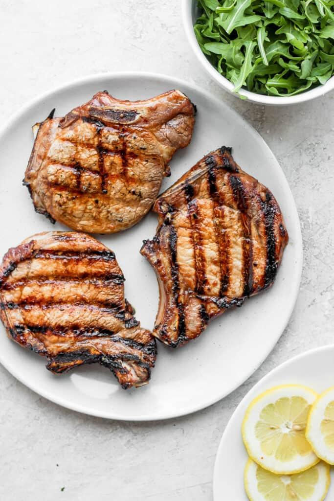 grilled pork chops on plate next to arugula