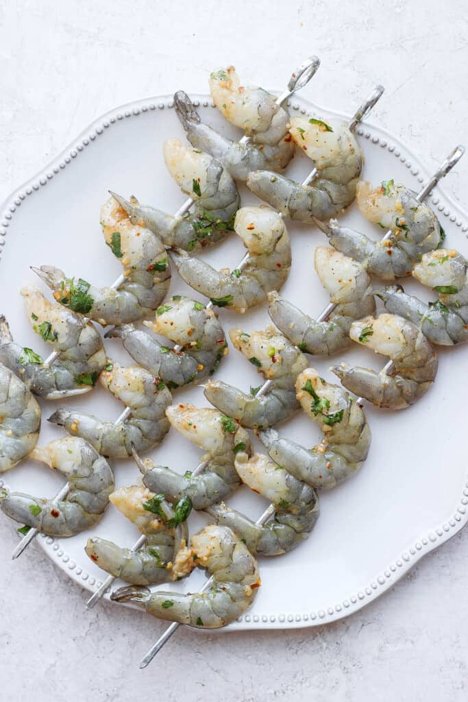 raw marinated shrimp on skewers on a plate