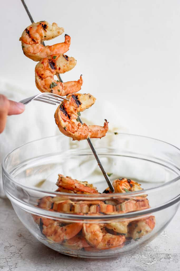 taking grilled shrimp off skewers and putting them into a bowl