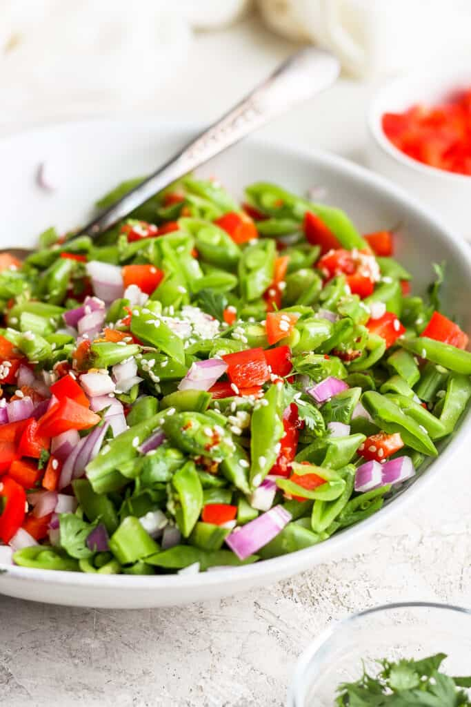 Ginger pea salad in a bowl topped with sesame seeds.