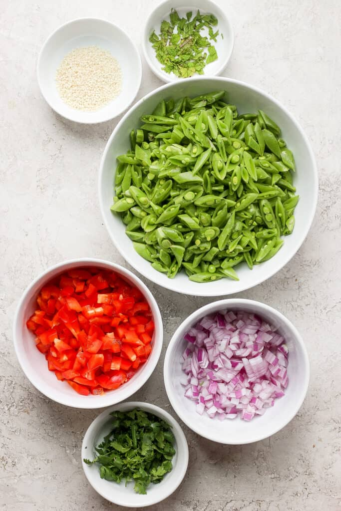 Sugar snap peas, red peppers, red onion, sesame seeds, and fresh mint in small bowls.