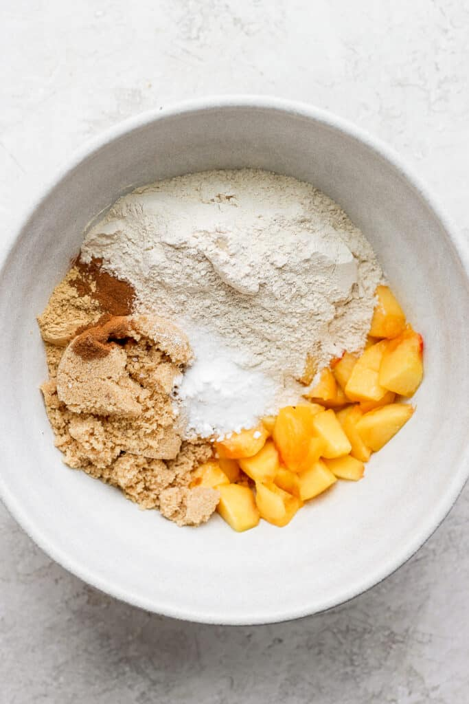 peach muffin ingredients in a bowl ready to be mixed together