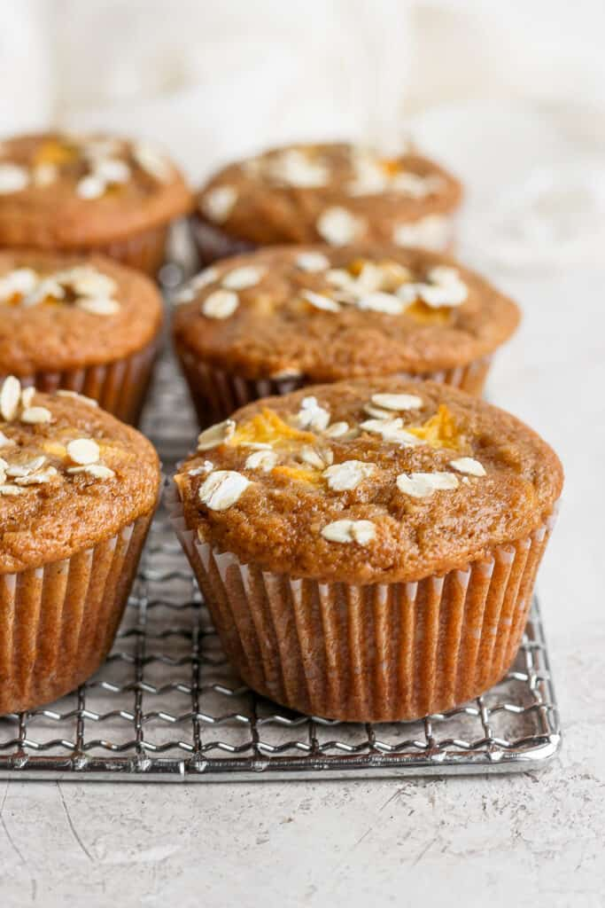 peach muffins on a cooling rack topped with rolled oats