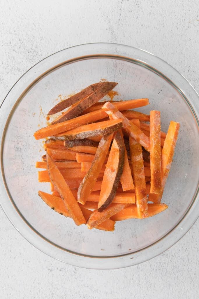 air fryer sweet potato fries in a bowl tossed with seasonings