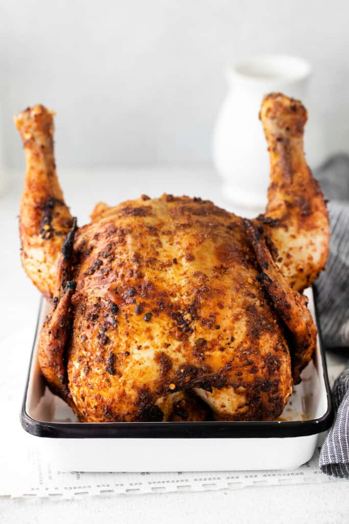 beer can chicken sitting in white pan