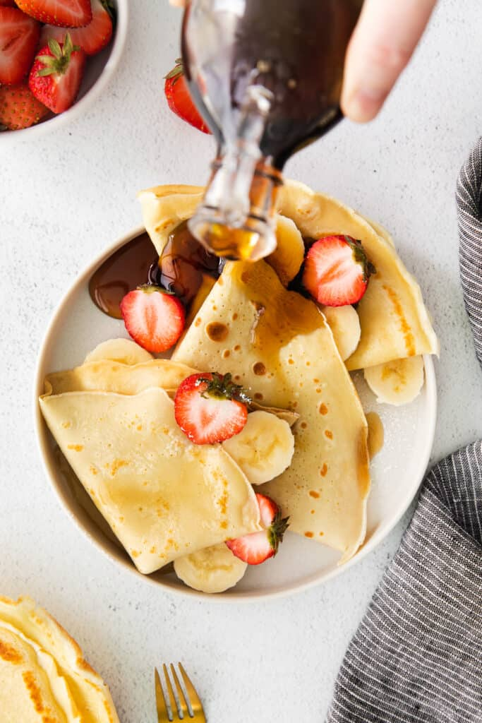 Drizzling maple syrup over crepes.