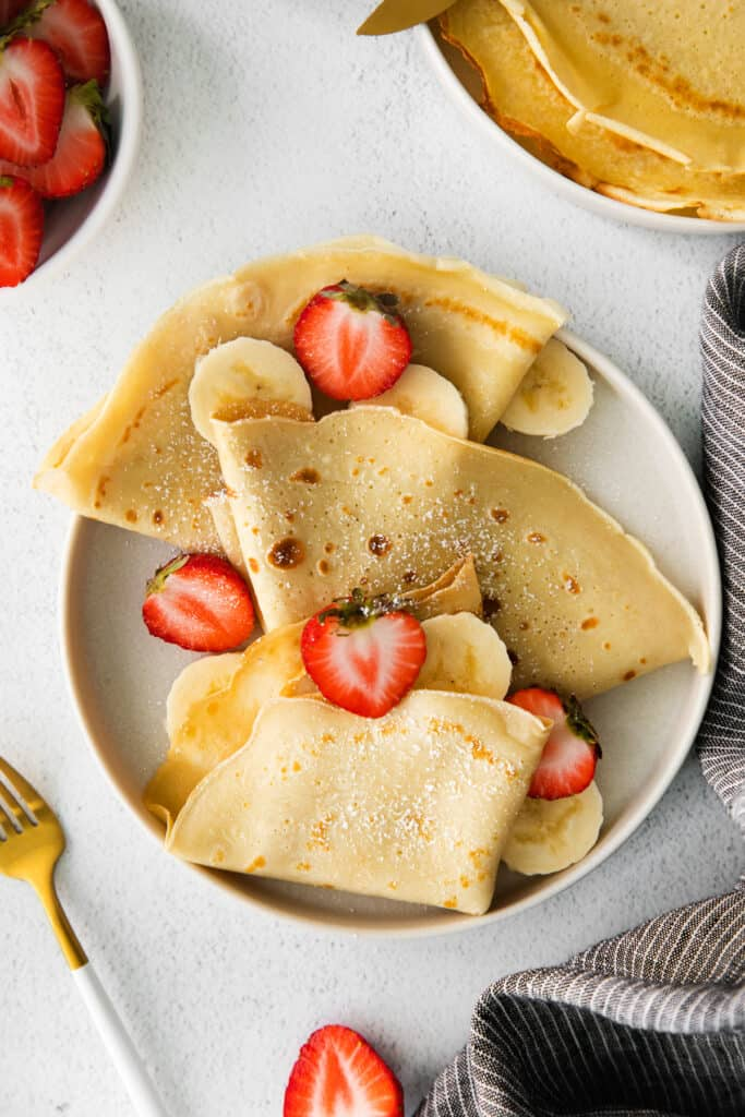 Crepes on a plate with strawberries and bananas.