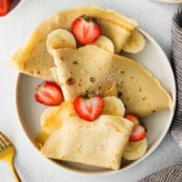 Crepes on a plate topping with strawberries and bananas.