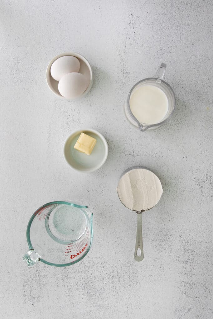 Milk, flour, butter, eggs, and water in small dishes.