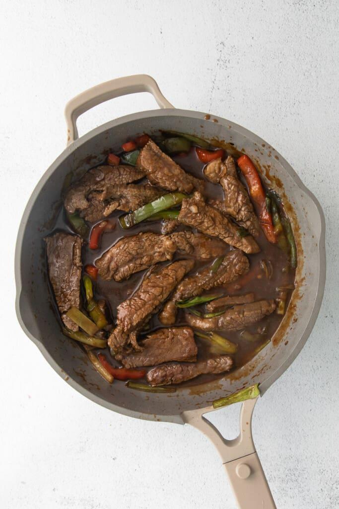 Pepper steak cooking in a fry pan.