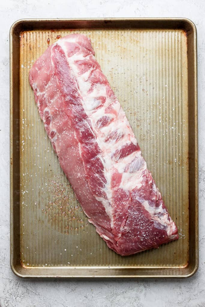 A slab of ribs on a baking sheet.