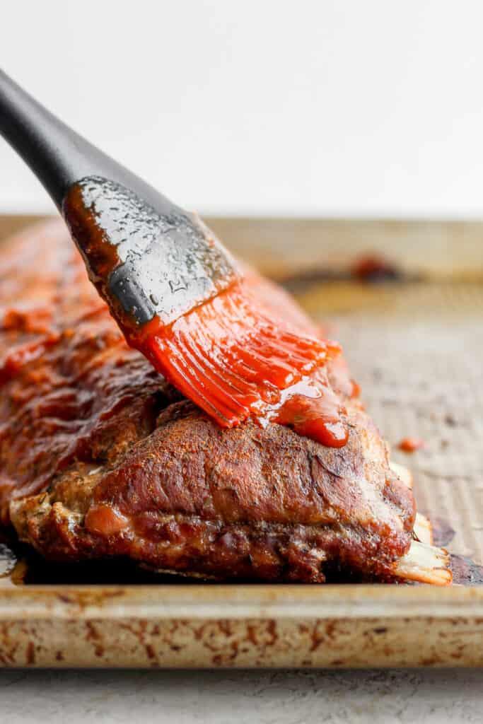 Brushing bbq sauce on ribs.