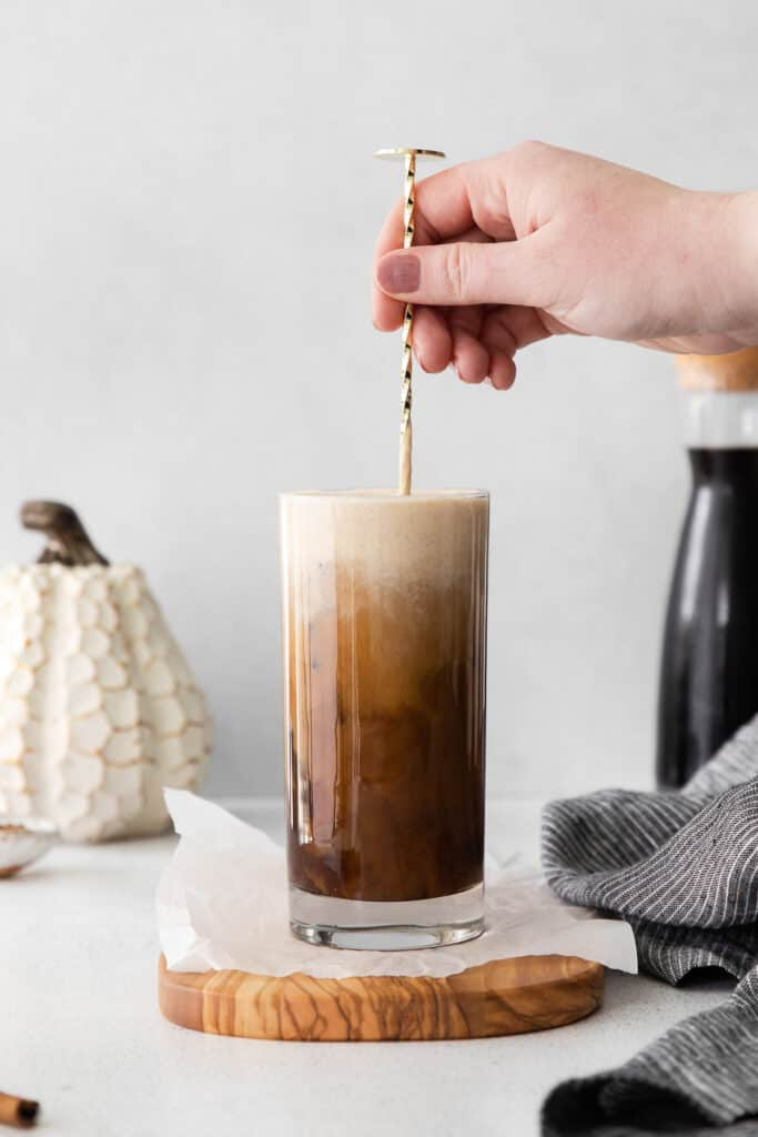 Mixing up Pumpkin Cream Cold Brew with a straw.