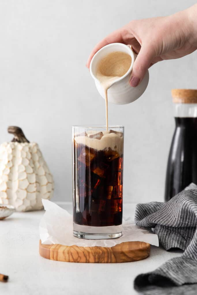 Pouring Pumpkin Cream Cold Brew over cold brew on ice.
