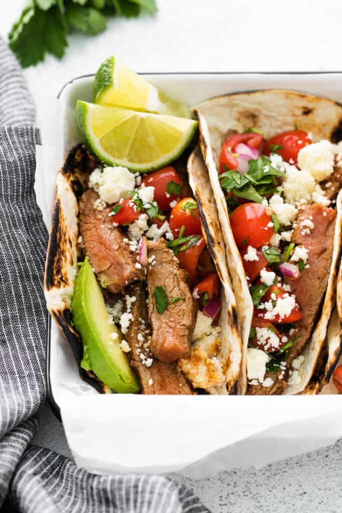close up photo of steak tacos garnished with fresh lime slices
