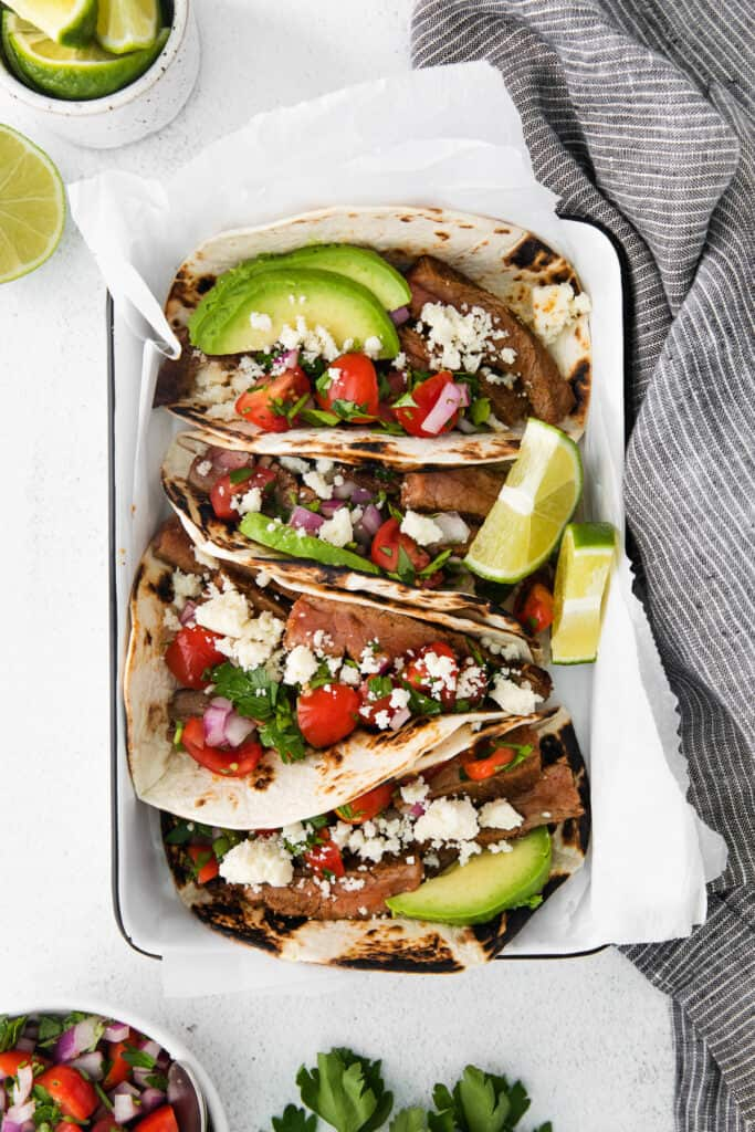 steak tacos topped with sliced avocado and cotija cheese